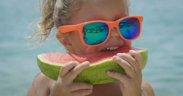 A little girl eats the watermelon on the beach to cool off and in the background you can see the sea
