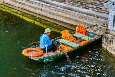 NINH BINH, VIETNAM - OCTOBER 21, 2018: Man is sitting on rowboat