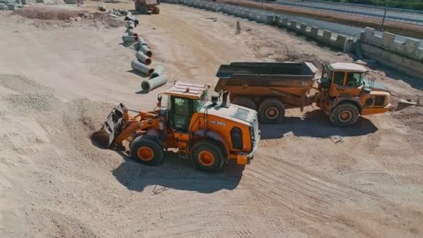 Luftaufnahme eines Großladers, der einen LKW auf einer Baustelle belädt