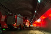 Fire trucks entering a large tunnel with red lights for rescue