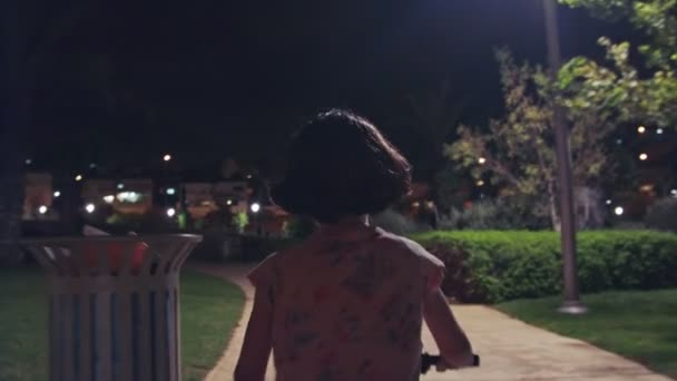 Little girl riding her bike in a park at night