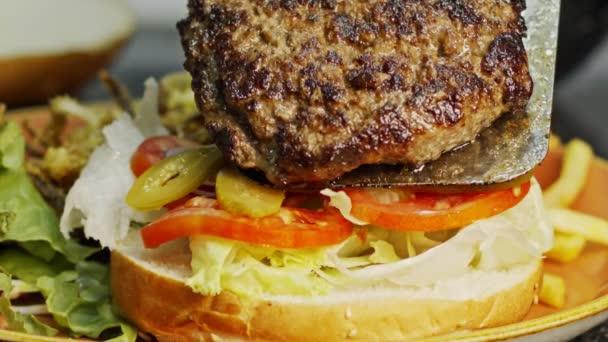 Velký hamburger na housce se zeleninou v pomalém pohybu