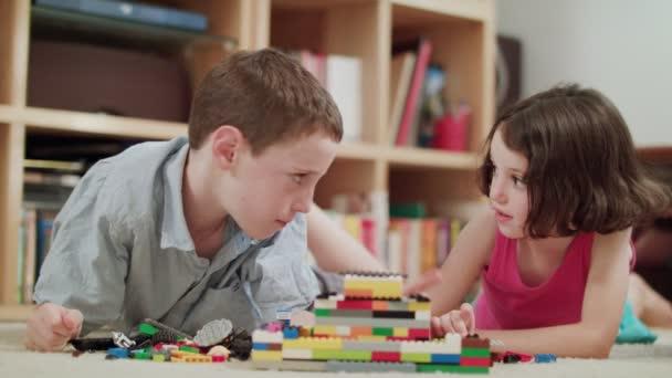 Dvě děti si hrají s lego kostkami doma