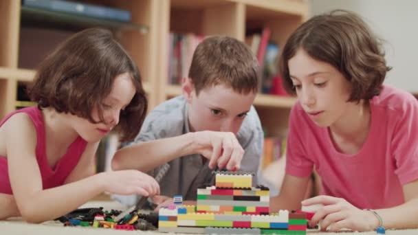 Tři děti hrát si s lego kostkami doma