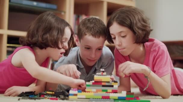 Három gyerek játék lego tégla otthon