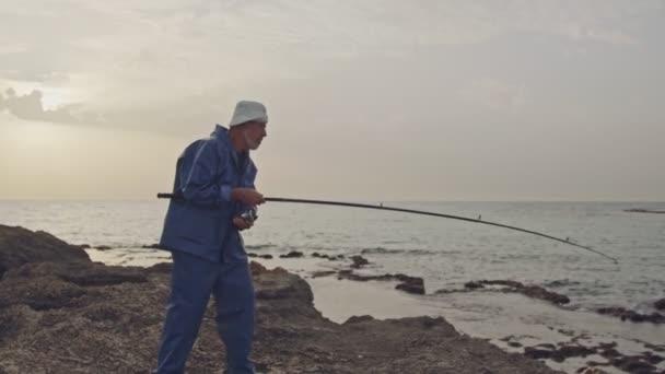 Starý rybář roste velká ryba, kterou chytil na pláži