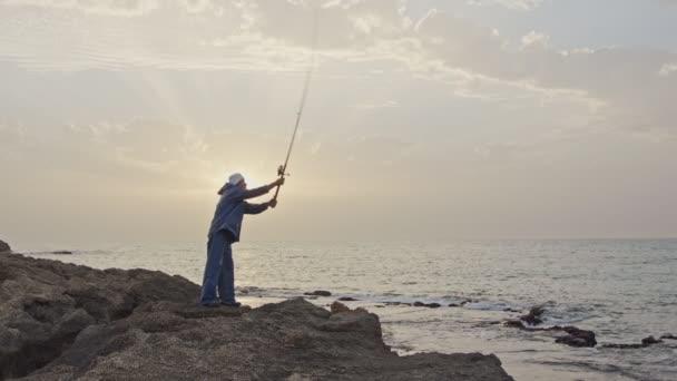 Starý rybář stojící na moři straně skály a rybaření před západem slunce