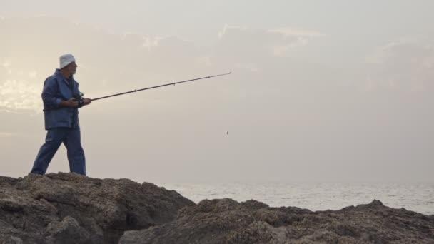 Starý rybář loví proti západu slunce