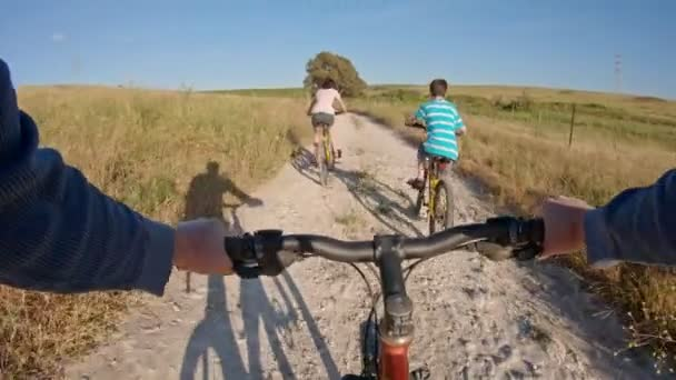 POV of two kids enjoying a bicycle ride on the countryside with their father