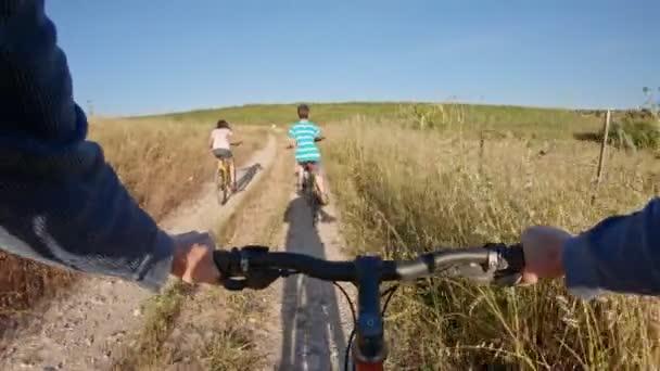 POV ze dvou dětí, které si užívají cyklistické jízdy na venkově se svým otcem