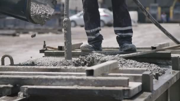 Dělníci nalévat beton do velkých ocelových molů na staveništi