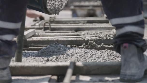 Arbeiter gießen auf einer Baustelle Beton in große Stahlformen