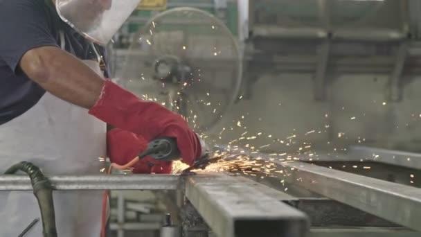 Pomalý pohyb pracovníka pomocí kovové brusky s jiskřičky v kovové prodejně