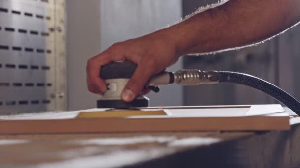 Pomalý pohyb pracovníka lešticí dveře skříňky v továrně na nábytek