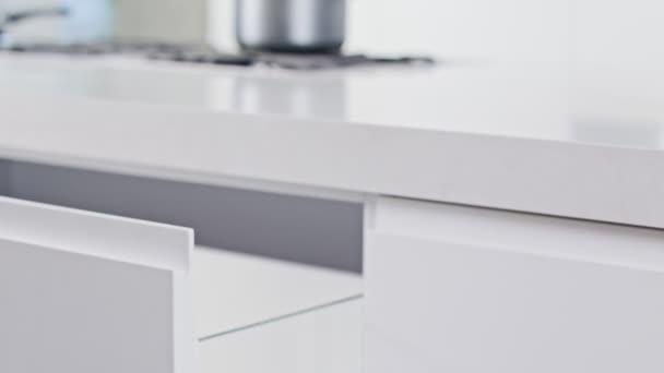 Blízká bílá moderní luxusní kuchyňská zásuvka se uzavírá pomalu