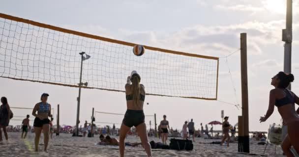 Lassú mozgás a nők játszanak strandröplabda alatt naplemente