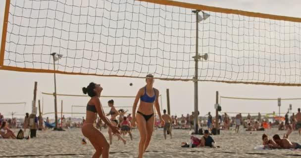 Pomalý pohyb žen hrající plážový volejbal během západu slunce