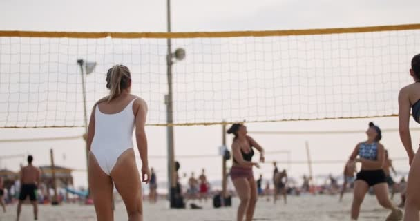 Slow motion of women playing beach volleyball during sunset
