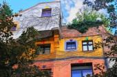 Fényképek Hundertwasser ház, Hundertwasserhaus - apartmanház, gondolatát és koncepcióját valamint osztrák művész Friedensreich Hundertwasser. Egyre nagyobb a fák, őszi színes homlokzat. Töredék dekoráció megtekintése