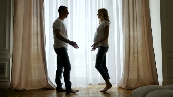 man comes to a pregnant womans wife at the window in silhouettes
