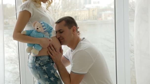 guy kisses the belly of his pregnant blonde wife standing