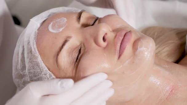 Kosmetikerin entfernt Make-up-Patientin, die auf einem speziellen Tisch liegt