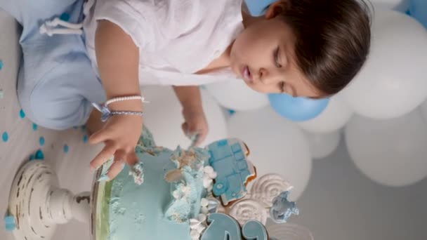 boy child of two years eating a festive blue cake with a car