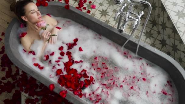 szexi lány rejlik egy nagy kő fürdő Rózsa virág a kezében