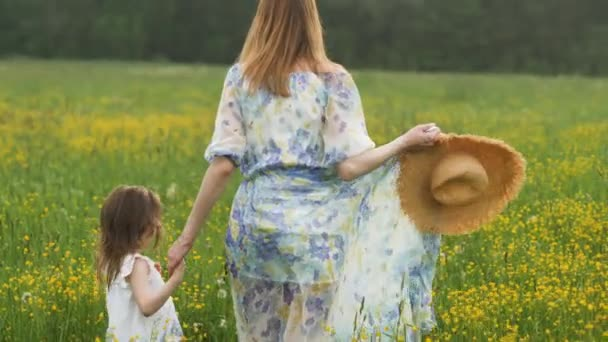 mother in a long dress walks on a yellow flower field in summer