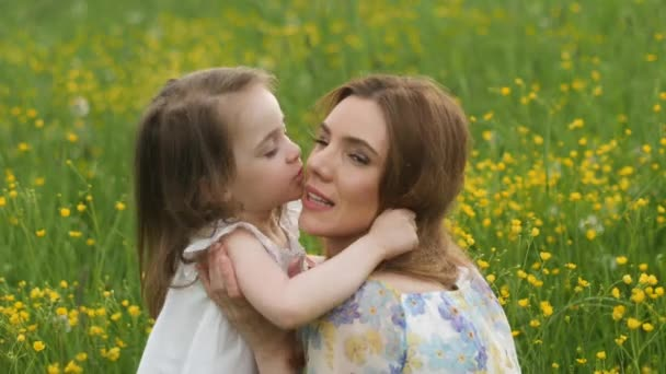 mother and daughter walk in a yellow field in the summer