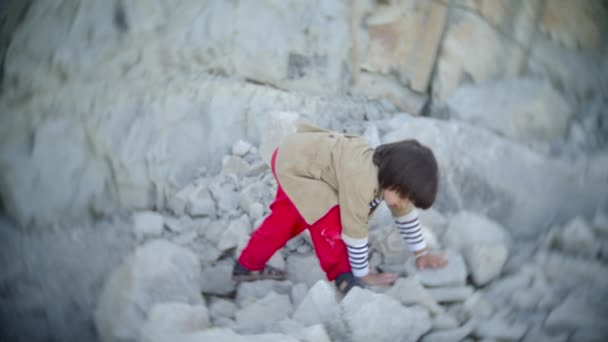 child a boy in red trousers a vest crawls on a rock