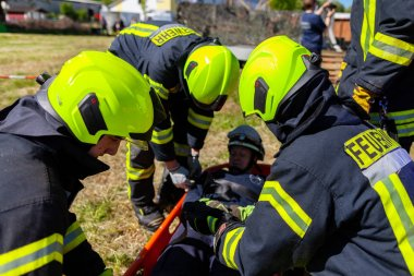 DELMENHORST / GERMANY - MAY 6, 2018: German firefighters  train a patient transport on a meadow. Feuerwehr means german fire department.