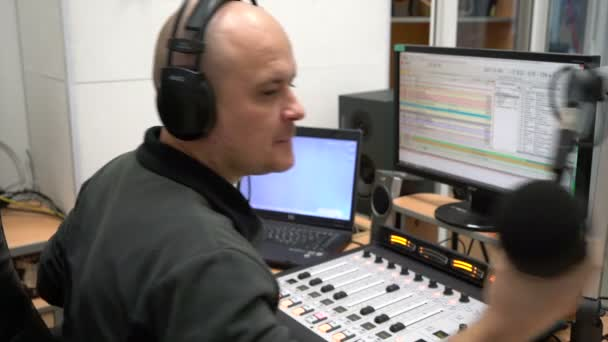 Man radio DJ sits at the remote equalizer of a computer radio station in  headphones and speaks into the microphone
