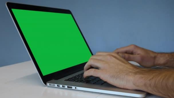 Zblízka střílel z notebooku rukama muže psát s modré zdi a zelené pozadí na monitoru jako zástupný symbol nahradit.