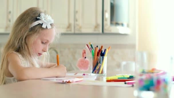 Egy aranyos kislány ül az íróasztalon, és felhívja a ceruza