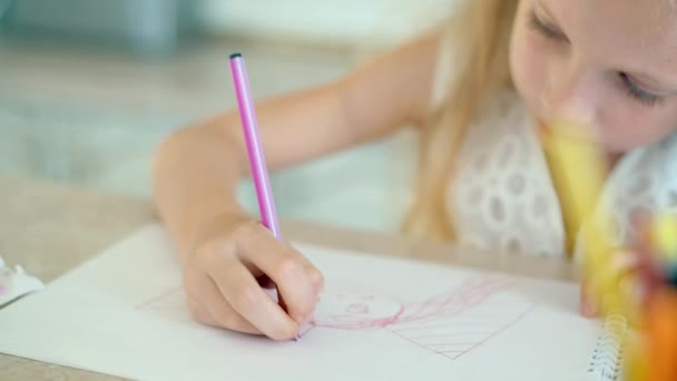 Cute little girl sits at the table and draws with pencils.