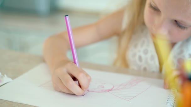 Roztomilá holčička sedí u stolu a kreslí tužkami.