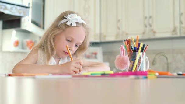 Roztomilá holčička sedí u stolu a kreslí tužkami
