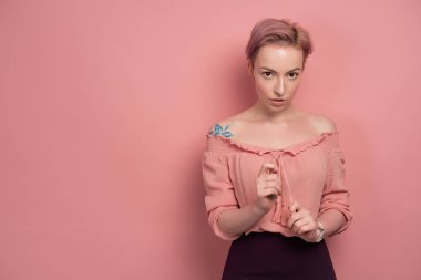 A girl with short pink hair stands sipping the ties of a blouse, on a pink background and looking at the camera.