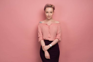 A girl with short pink hair in a blouse with bare shoulders and a black skirt stands on a pink background and looks at the camera.