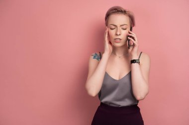 A girl with short pink hair and a tattoo in a gray top closed her eyes tensely, speaks on the phone, on a pink background.