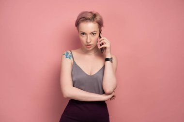 A girl with short pink hair and a tattoo on his shoulder in a gray top speaks on the phone on a pink background.