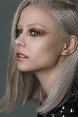 Beautiful platinum blonde with bright bronze eye makeup.