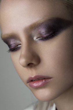 Close portrait of a platinum blonde with bright eye makeup in purple tones with a metallic glow.