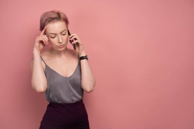 A girl with short pink hair and a tattoo in a gray top and speaks on the phone, listening carefully, on a pink background.