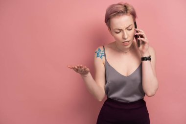 A girl with short pink hair and a tattoo in a gray top speaks displeasedly on the phone, standing on a pink background.