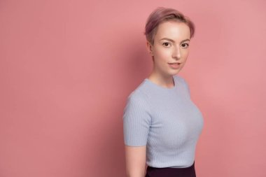 A girl with short pink hair in a T-shirt is standing in a half-turn on a pink background and looking at the camera.