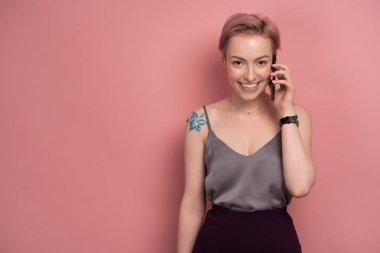 A girl with short pink hair and a tattoo on his shoulder in a gray top smiling speaks on the phone on a pink background.