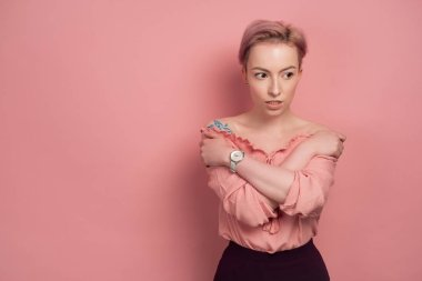 A girl with short pink hair stands in a blouse on a pink background, hugging herself over the shoulders and looks to the side.