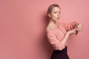 A girl with short pink hair in a blouse with bare shoulders looks at the camera, pointing to the clock, on a pink background.